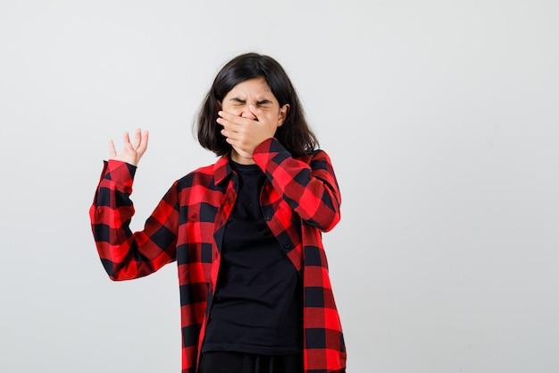 Menina adolescente em t-shirt, camisa quadriculada, segurando a mão na boca enquanto mostra o gesto de pare e olhando com nojo, vista frontal.
