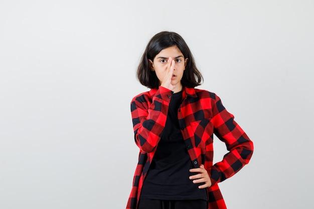 Menina adolescente em t-shirt, camisa quadriculada, segurando a mão perto da boca para contar o segredo e olhando cuidadosa, vista frontal.
