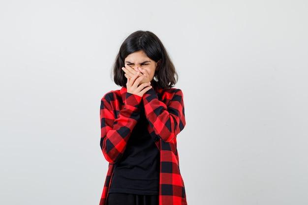 Menina adolescente em t-shirt, camisa quadriculada, segurando as mãos na boca e olhando com nojo, vista frontal.