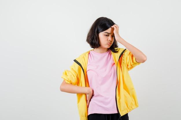 Menina adolescente em t-shirt, jaqueta coçando a cabeça e olhando pensativa, vista frontal.