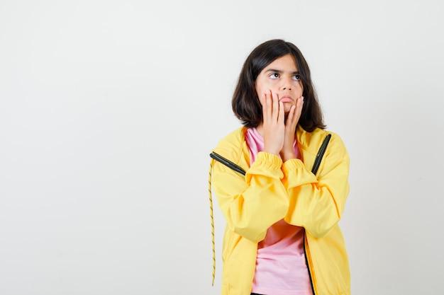 Menina adolescente em t-shirt, jaqueta de mãos dadas perto da boca e olhando atenta, vista frontal.