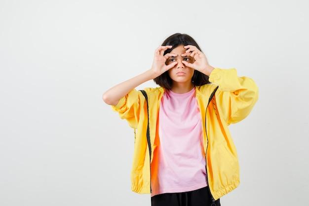 Menina adolescente em t-shirt, jaqueta, olhando por entre os dedos e parecendo chateada, vista frontal.