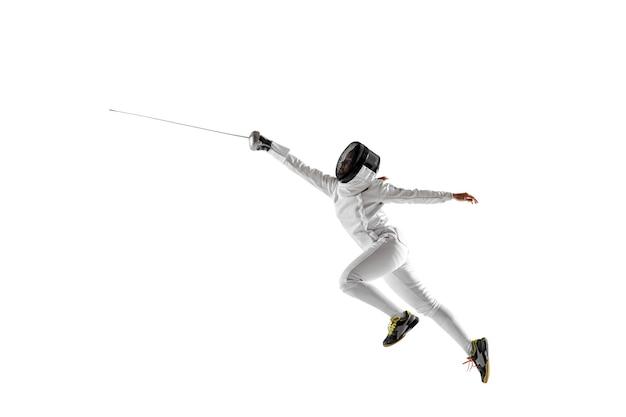 Menina adolescente em traje de esgrima com espada na mão, isolada no fundo branco.