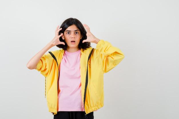 Menina adolescente em um agasalho amarelo, camiseta de mãos dadas perto do rosto e parecendo chocada, vista frontal.