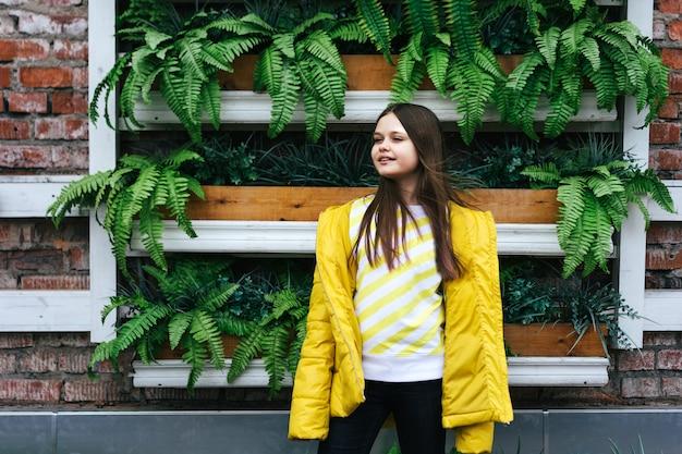 Menina adolescente, em, um, amarela, casaco, e, um, sweatshirt, ligado, a, fundo, de, um, cerca, de, plantas