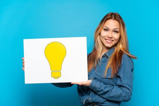 Menina adolescente em um fundo azul isolado segurando um cartaz com o ícone de lâmpada com uma expressão feliz