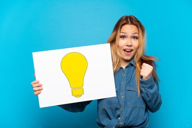 Menina adolescente em um fundo azul isolado segurando um cartaz com o ícone de lâmpada e comemorando uma vitória