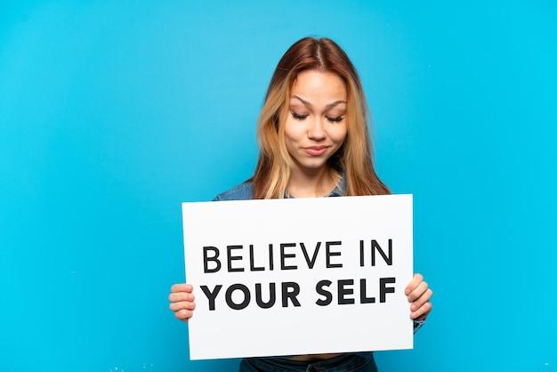 Menina adolescente em um fundo azul isolado segurando um cartaz com o texto acredite em si mesmo