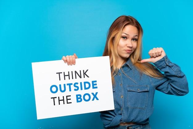 Menina adolescente em um fundo azul isolado segurando um cartaz com o texto pense fora da caixa com um gesto orgulhoso