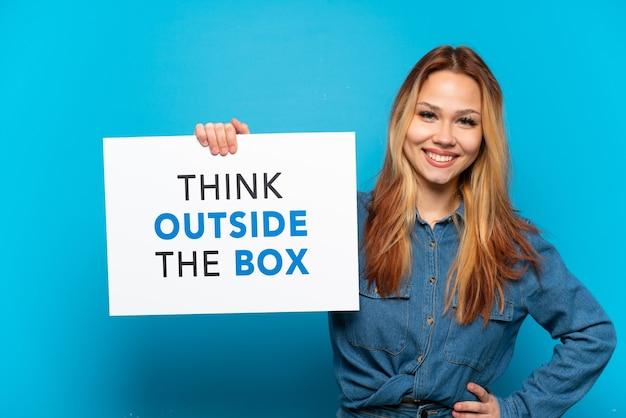 Menina adolescente em um fundo azul isolado segurando um cartaz com o texto pense fora da caixa com uma expressão feliz