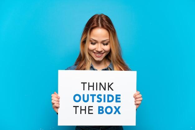 Menina adolescente em um fundo azul isolado segurando um cartaz com o texto pense fora da caixa