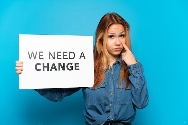 Menina adolescente em um fundo azul isolado segurando um cartaz com o texto precisamos de uma mudança e mostrando algo