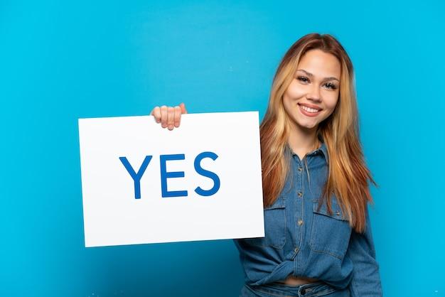 Menina adolescente em um fundo azul isolado segurando um cartaz com o texto sim com uma expressão feliz