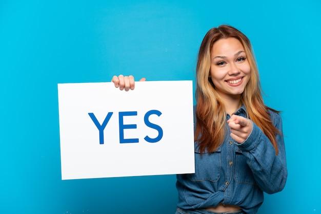 Menina adolescente em um fundo azul isolado segurando um cartaz com o texto sim e apontando-o
