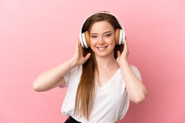 Menina adolescente em um fundo rosa isolado ouvindo música