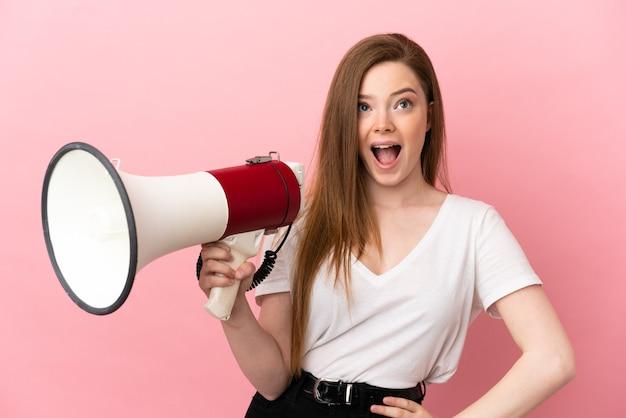 Menina adolescente em um fundo rosa isolado segurando um megafone e com expressão de surpresa