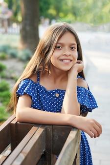Menina adolescente em um vestido azul caminha no parque de verão ao pôr do sol