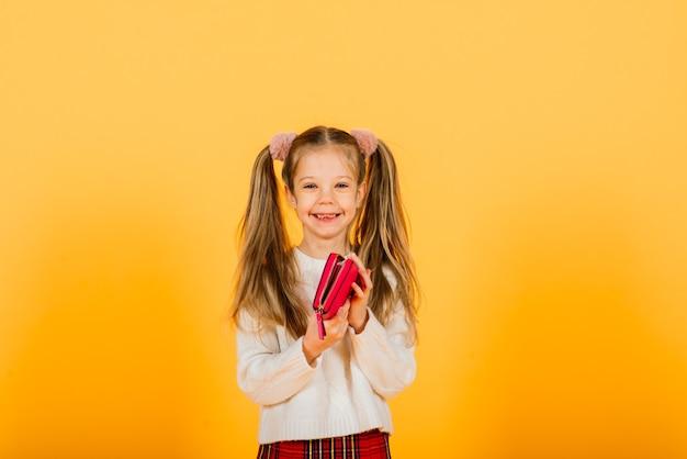 Menina adolescente em uma parede amarela segurando uma carteira