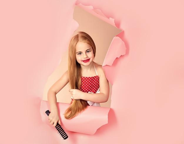 Menina adolescente em vestido vintage segura escova. cabelo longo. salão de beleza infantil. cuidados com o cabelo e shampoo.