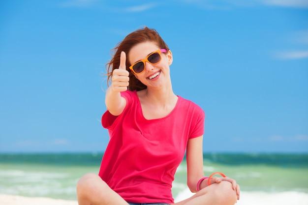 Menina adolescente engraçada que senta-se na areia na praia.