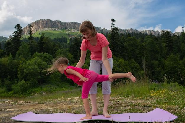 Menina adolescente ensina uma criança a fazer exercícios de ioga na natureza em um fundo de montanhas