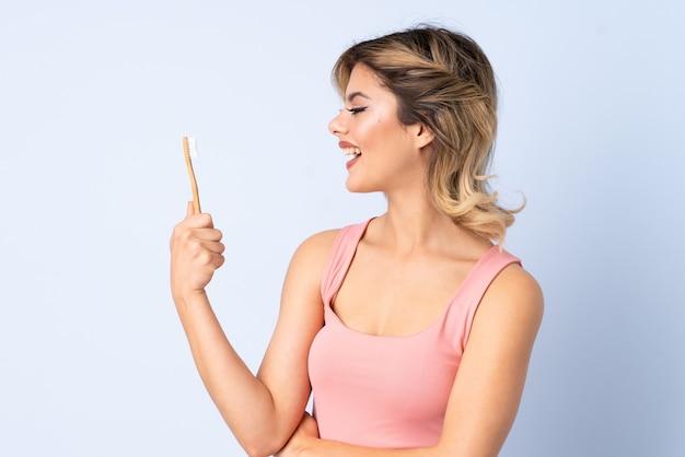 Menina adolescente escovando os dentes com uma expressão feliz