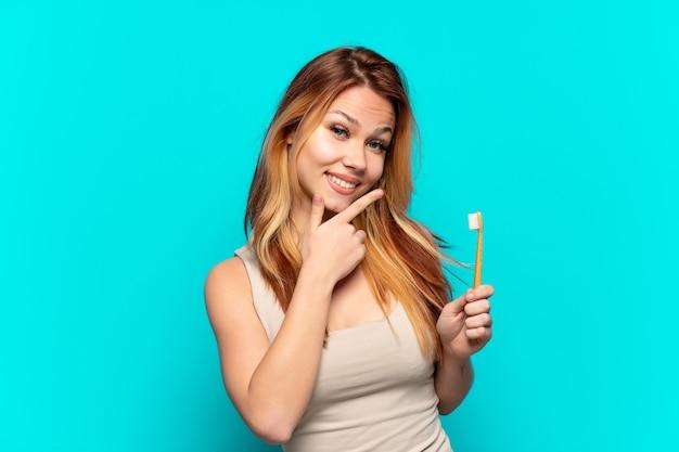 Menina adolescente escovando os dentes em um fundo azul isolado feliz e sorridente
