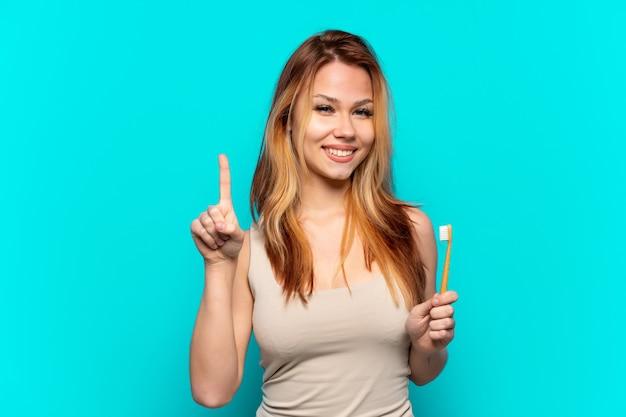 Menina adolescente escovando os dentes em um fundo azul isolado, mostrando e levantando um dedo em sinal dos melhores