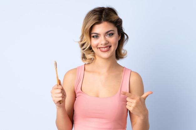 Menina adolescente escovando os dentes isolados no azul com expressão facial surpresa