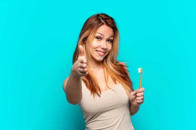 Menina adolescente escovando os dentes sobre um fundo azul isolado apertando as mãos para fechar um bom negócio