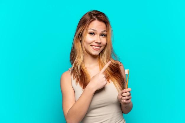 Menina adolescente escovando os dentes sobre um fundo azul isolado apontando para o lado para apresentar um produto