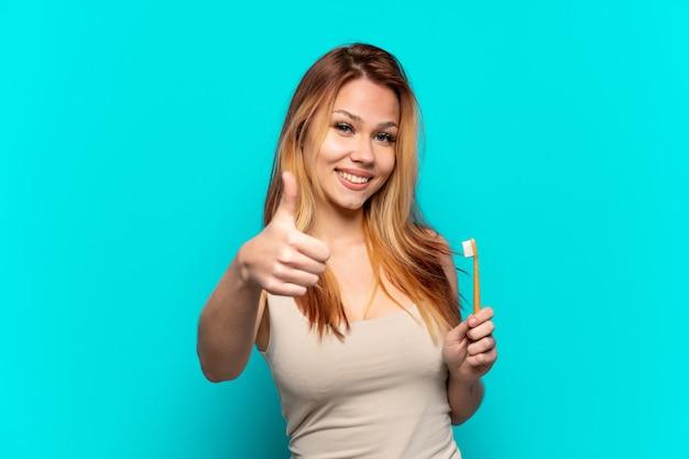 Menina adolescente escovando os dentes sobre um fundo azul isolado com o polegar levantado porque algo bom aconteceu