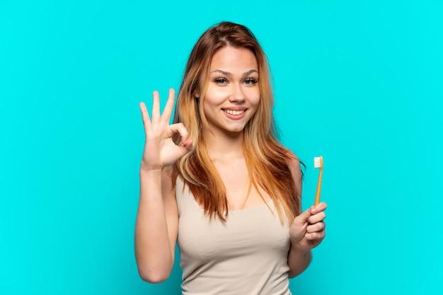 Menina adolescente escovando os dentes sobre um fundo azul isolado e mostrando um sinal de ok com os dedos