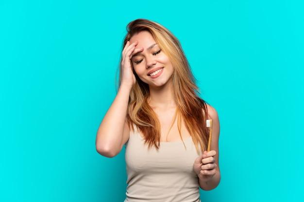 Menina adolescente escovando os dentes sobre um fundo azul isolado e sorrindo muito