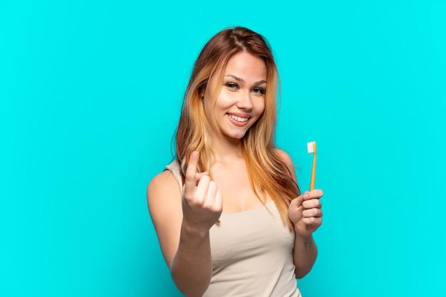 Menina adolescente escovando os dentes sobre um fundo azul isolado fazendo um gesto próximo
