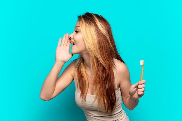 Menina adolescente escovando os dentes sobre um fundo azul isolado gritando com a boca bem aberta para o lado