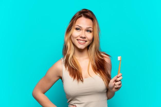 Menina adolescente escovando os dentes sobre um fundo azul isolado, posando com os braços no quadril e sorrindo