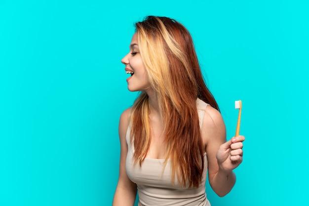 Menina adolescente escovando os dentes sobre um fundo azul isolado rindo na posição lateral