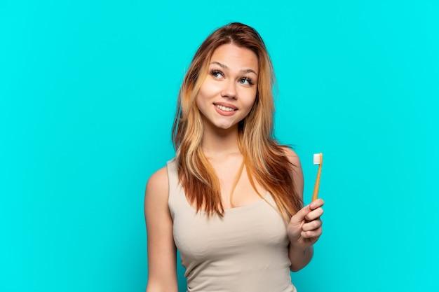 Menina adolescente escovando os dentes sobre um fundo azul isolado tendo uma ideia enquanto olha para cima