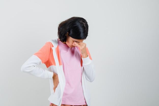 Menina adolescente esfregando os olhos na jaqueta, camisa rosa e parecendo estressante.