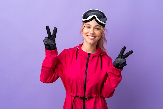 Menina adolescente esquiadora com óculos de snowboard na parede roxa isolada, mostrando o sinal da vitória com as duas mãos