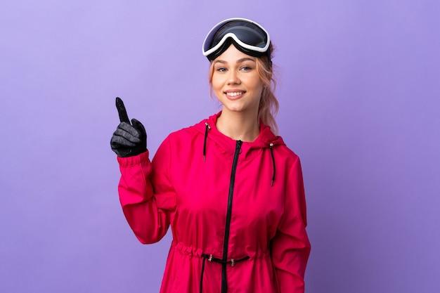 Menina adolescente esquiadora com óculos de snowboard sobre uma parede roxa isolada, mostrando e levantando um dedo em sinal dos melhores