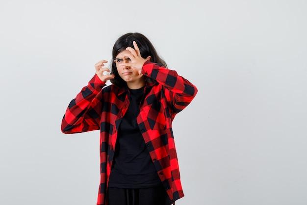 Menina adolescente esticando as mãos de maneira agressiva na camisa casual e olhando furiosa, vista frontal.