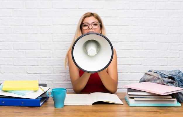 Menina adolescente estudante em dentro de casa gritando através de um megafone