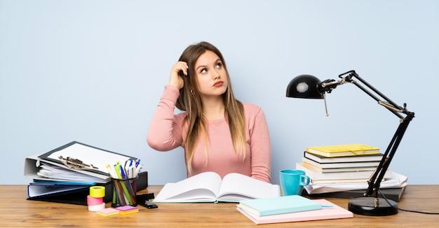 Menina adolescente estudante em seu quarto com dúvidas e com expressão de rosto confuso