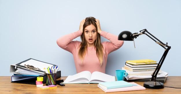 Menina adolescente estudante em seu quarto com expressão facial de surpresa