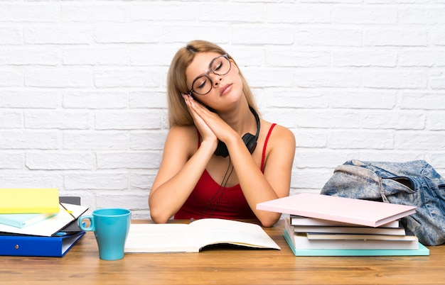 Menina adolescente estudante no interior fazendo gesto de sono na expressão dorable