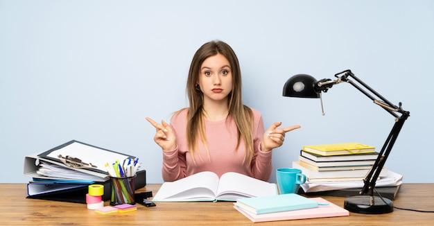 Menina adolescente estudante no quarto dela apontando para as laterais tendo dúvidas