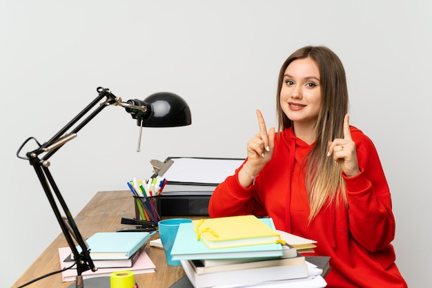 Menina adolescente estudante no quarto dela, apontando para uma ótima idéia