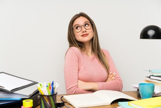 Menina adolescente estudante no quarto dela fazendo dúvidas gesto enquanto levantando os ombros